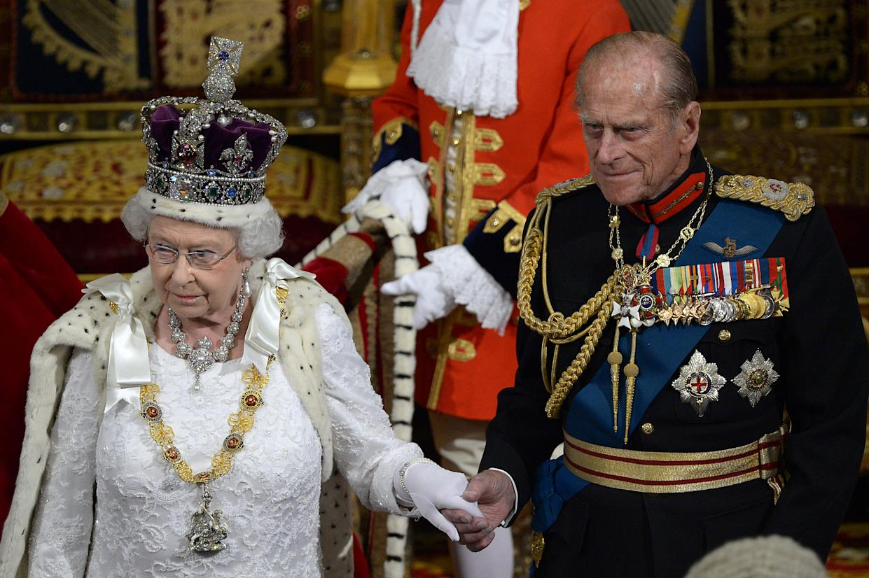 Britain's Queen Elizabeth II (L) and Prince Philip, Duke of Edinburgh (R) leave the House of Lords after delivering the Queen's Speech during the State Opening of Parliament at the Palace of Westminster in London on June 4, 2014. The State Opening of Parliament marks the formal start of the parliamentary year and the Queen's Speech sets out the governments agenda for the coming session.  AFP PHOTO / POOL / CARL COURT (Photo by CARL COURT / POOL / AFP) (Photo by CARL COURT/POOL/AFP via Getty Images)