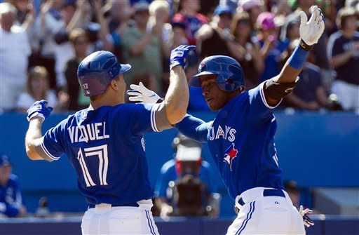 Toronto Blue Jays' Adeiny Hechavarria, right, celebrates his two-run home run with teammate Omar Vizquel during seventh inning of a baseball game against the Boston Red Sox in Toronto on Sunday, Sept. 16, 2012. (AP Photo/The Canadian Press, Nathan Denette)