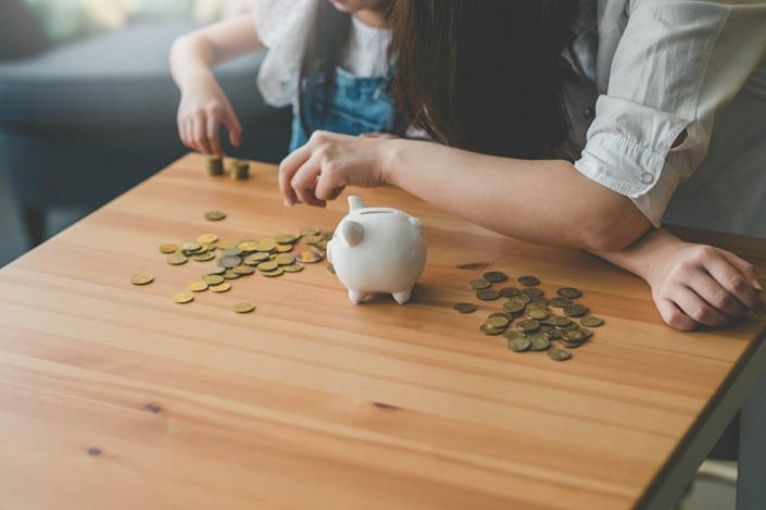 An image of a mother and her daughter counting coins from a piggy bank.