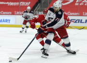 Columbus Blue Jackets left wing Nick Foligno (71) clears the puck against Detroit Red Wings center Vladislav Namestnikov (92) during the first period of an NHL hockey game Tuesday, Jan. 19, 2021, in Detroit. (AP Photo/Duane Burleson)