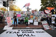 <p>Many Trump critics flocked to the White House in recent days (right: some wave flags at Black Lives Matter Plaza on Friday) and turned the fencing around it into an ode to anti-Trump sentiment as Biden looked poised to oust him from office.</p>