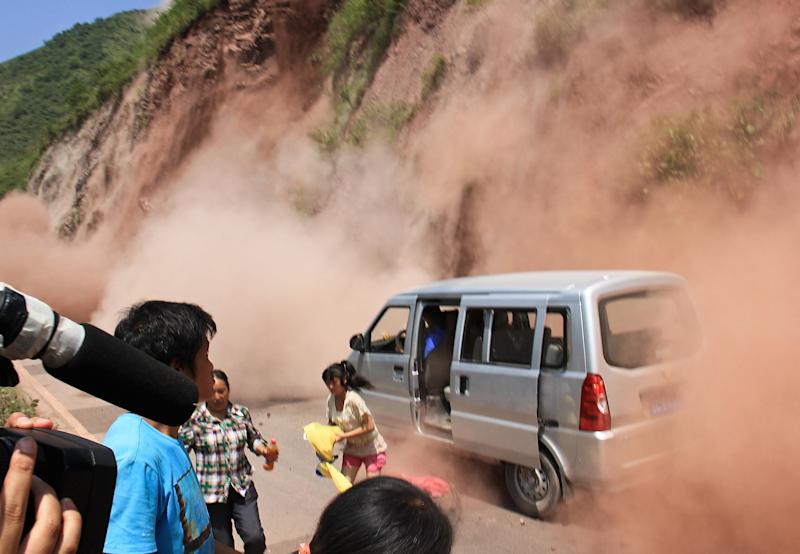 People run as fallen rocks land near their vehicle after the area was hit by earthquake in Zhaotong town, Yiliang County, southwest China's Yunnan Province, Friday, Sept. 7, 2012. A series of earthquakes collapsed houses and triggered landslides Friday in a remote mountainous part of southwestern China where damage was preventing rescues and communications were disrupted. At least 64 deaths have been reported. (AP Photo) CHINA OUT