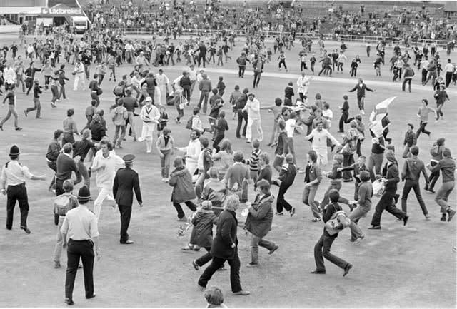 Bob Willis leads England off the Headingley pitch after their victory in 1981 as fans run on to celebrate (PA).