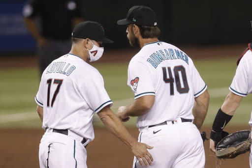 Arizona Diamondbacks starting pitcher Madison Bumgarner (40) is pulled from the game by manager Torey Lovullo (17) during the fifth inning of a baseball game against the Houston Astros Tuesday, Aug. 4, 2020, in Phoenix. (AP Photo/Matt York)