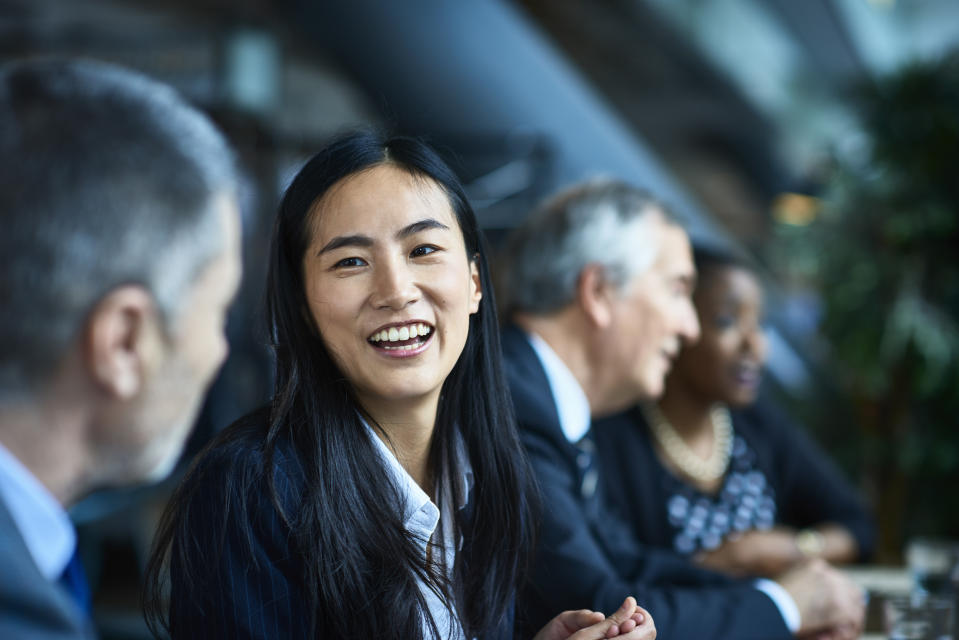 Close up portrait of Asian businesswoman, beside male senior coworker, smiling and laughing, respect, admiration