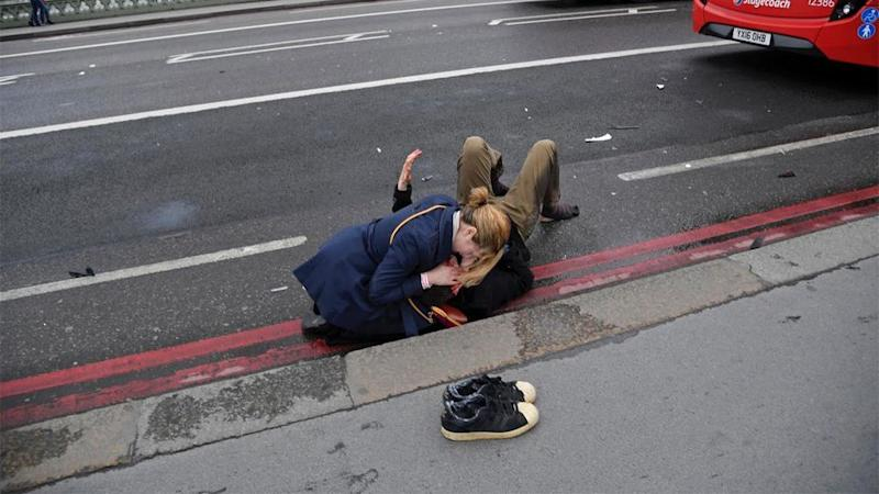 A woman holds a seriously injured man on Westminster Bridge. Source: Reuters