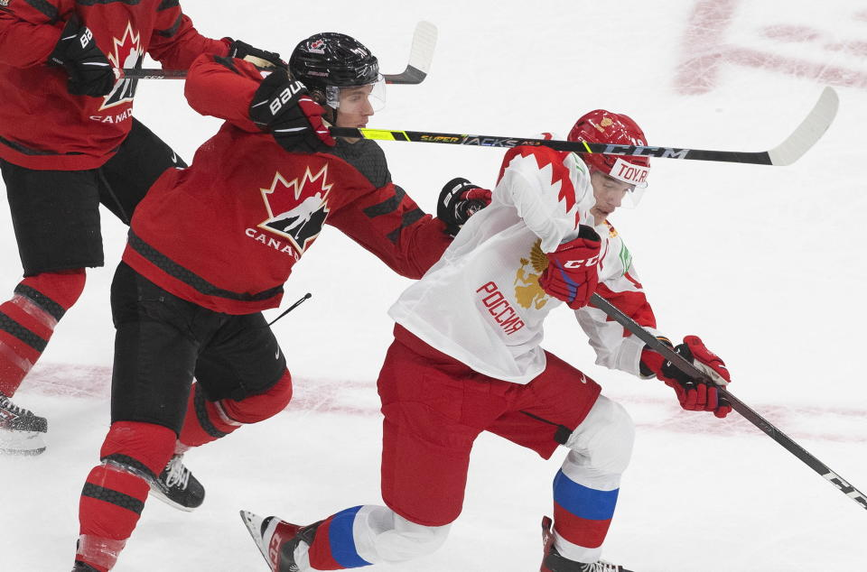 Canada's Dylan Holloway (10) and Russia's Vasili Podkolzin (19) compete for the puck during the first period of a game leading up to the IIHF World Junior Hockey Championships, Wednesday, Dec. 23, 2020, in Edmonton, Alberta. (Jason Franson/The Canadian Press via AP)
