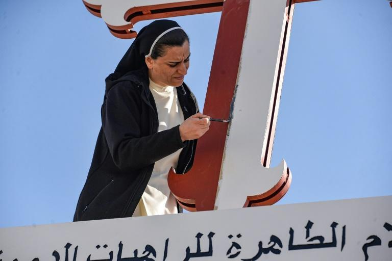 A nun adds a coat of paint to a cross of the Immaculate Mary Dominican Sisters Convent in the predominantly Christian town of Qaraqosh near Mosul