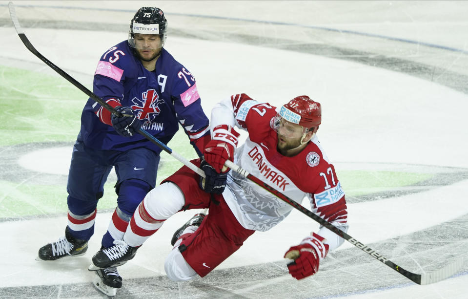 Robert Dowd of Britain, left, and Nicklas Jensen of Denmark fight for a puck during the Ice Hockey World Championship group A match between Britain and Denmark at the Olympic Sports Center in Riga, Latvia, Tuesday May 25, 2021. (AP Photo/Roman Koksarov)