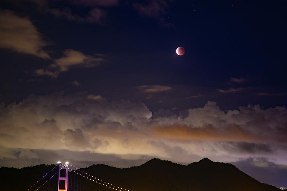 HONG KONG, CHINA - 2021/05/26: A reddish blood moon is seen above the Tsing Ma Bridge in Hong Kong. A reddish blood supermoon eclipse appears in the night sky of Hong Kong tonight. The last super blood moon visible in Hong Kong was 21 years ago. (Photo by Dominic Chiu/SOPA Images/LightRocket via Getty Images)