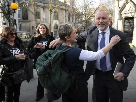 Harry Miller, founder of the campaign group Fair Cop, greets supporters outside the High Court (PA)