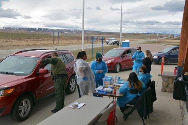A U.S. Border Patrol agent directs a driver after the passenger received a COVID-19 vaccine from nurses at the mobile clinic on April 29, 2021.