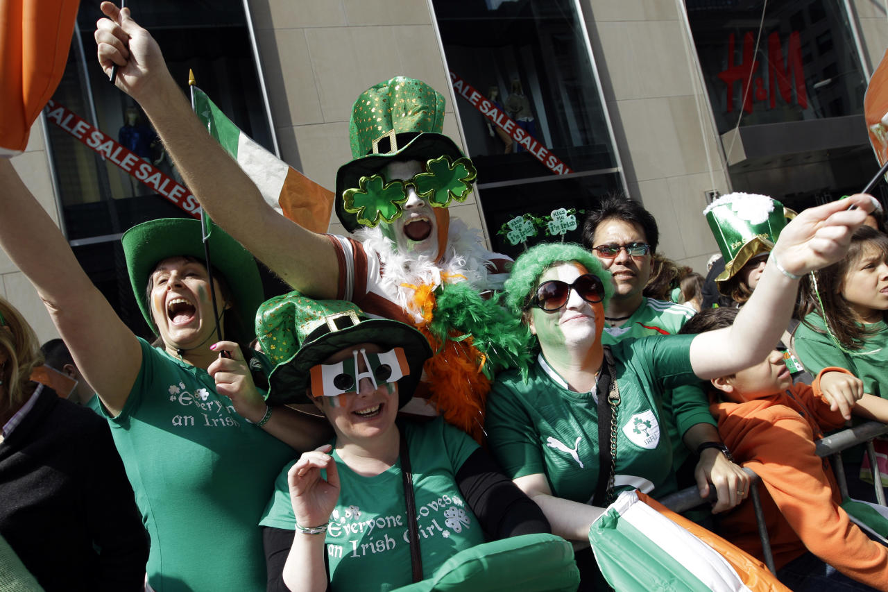 Deirdre Kelly, left, Linda Forth, second from left, Darren McCarthy, center, and Eimear Ni Bhriain, of Dublin, Ireland, cheer on the marchers during the 251st annual St. Patrick's Day Parade, Saturday, March 17, 2012 in New York. (AP Photo/Mary Altaffer)