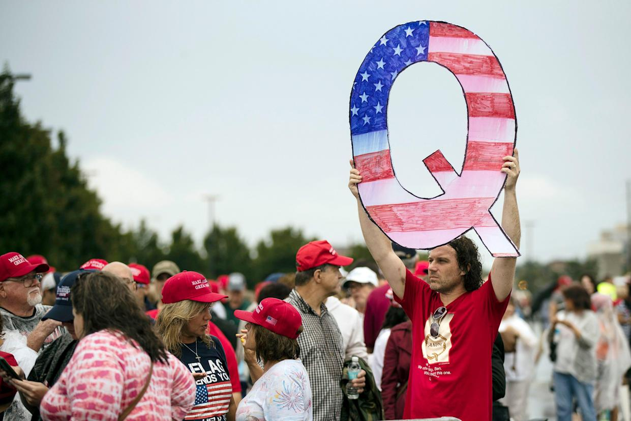 FILE - In this Aug. 2, 2018, file photo, a protesters holds a Q sign waits in line with others to enter a campaign rally with President Donald Trump in Wilkes-Barre, Pa.