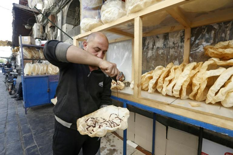 "A Syrian vendor spreads grape molasses on a traditional sweet known as ""naeem"", a traditional treat served during Ramadan"
