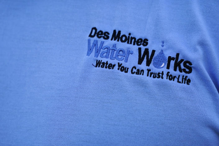 The Des Moines Water Works logo is seen on employee Bill Blubaugh's shirt as he collects a water sample from the Raccoon River, Thursday, June 3, 2021, in Des Moines, Iowa. Each day the utility analyzes samples from the Raccoon River and others from the nearby Des Moines River as it works to deliver drinking water to more than 500,000 people in Iowa's capital city and its suburbs. (AP Photo/Charlie Neibergall)