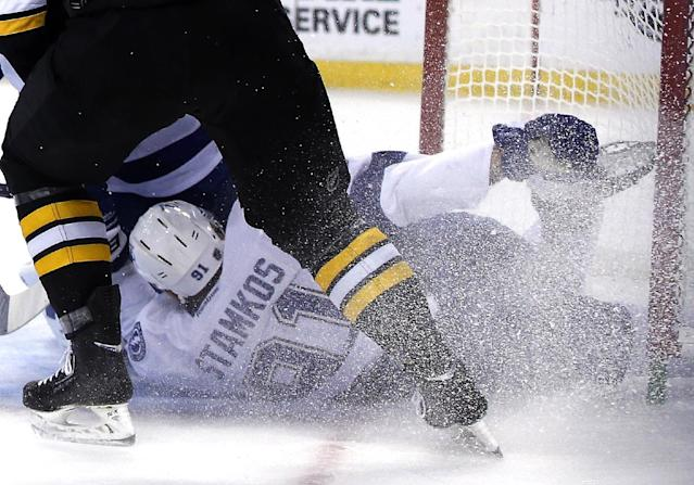 Tampa Bay Lightning center Steven Stamkos holds his skate after banging into the goalpost defending against Boston Bruins defenseman Dougie Hamilton, above, during the second period of an NHL hockey game in Boston Monday, Nov. 11, 2013. Stamkos was taken off the ice on a stretcher after the play. (AP Photo/Elise Amendola)
