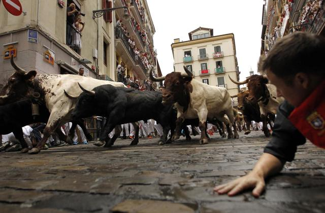 <p>Revellers run in front of Fuente Ymbro's fighting bulls during the running of the bulls at the San Fermin Festival, in Pamplona, northern Spain, July 10, 2017. (AP Photo/Alvaro Barrientos) </p>
