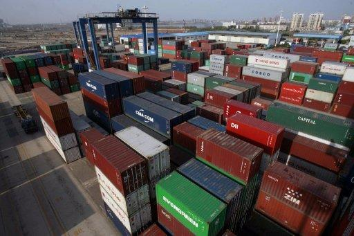 Shipping containers pile up at a container port in Wuhan, in central China's Hubei province. China swung back to a trade surplus last month, reversing a massive deficit recorded in February, the official Xinhua news agency said Tuesday