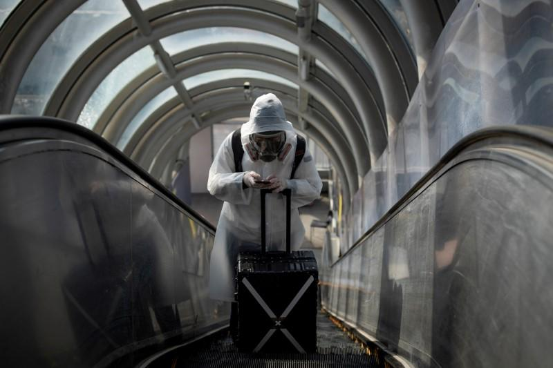 A traveller wearing protective clothing and a full-face mask goes up an escalator after leaving Beijing Railway Station as the country is hit by an outbreak of the novel coronavirus