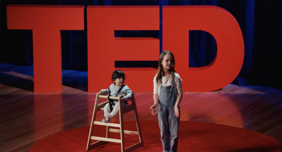 A screenshot from Molly Wright's TED talk showing her in front of th TED sign with her neighbour, baby Ari who she talked about in her talk.