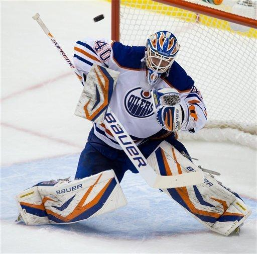 Edmonton Oilers goalie Devan Dubnyk makes a blocker save against the Vancouver Canucks during the second period of an NHL hockey game in Vancouver, British Columbia, on Sunday, Jan. 20, 2013. (AP Photo/The Canadian Press, Darryl Dyck)