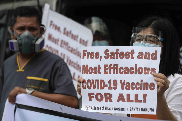 Health workers display slogans calling on the government to give them a vaccine with the safest, highest efficacy and effectivity during a a protest outside the Lung Center of the Philippines in Quezon city, Philippines on Monday, March 1, 2021. The Philippines launched a vaccination campaign Monday to contain one of Southeast Asia's worst coronavirus outbreaks but faces supply problems and public resistance, which it hopes to ease by inoculating top officials. (AP Photo/Aaron Favila)