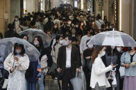 People wearing face masks to help curb the spread of the coronavirus walk in Osaka, western Japan, Monday, April 5, 2021. Semi-emergency coronavirus measures began in Osaka and its neighboring prefecture in western Japan and another prefecture in the north Monday as Japan tries to minimize the economic impact to specific areas where infections are rising back less than four months before the Tokyo Olympics.(Kyodo News via AP)
