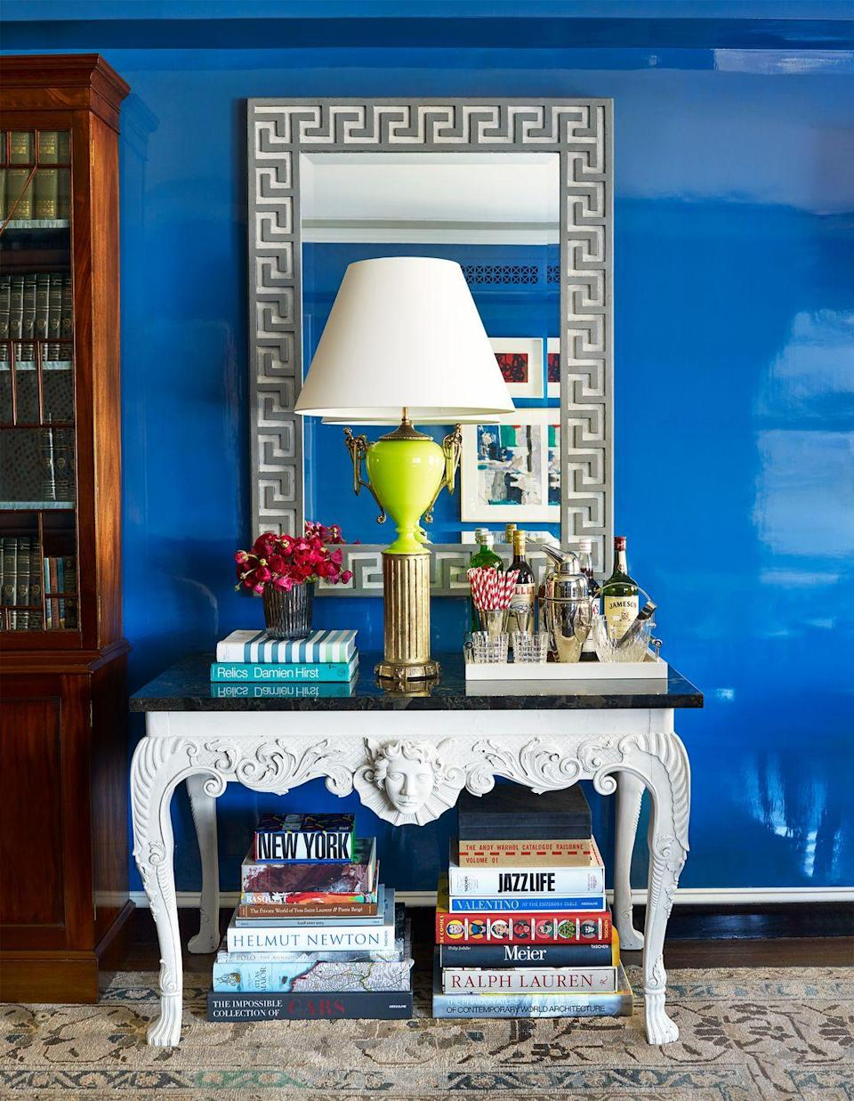 <p>Or, here's a third idea that requires no additional pieces of furniture at all: Simply stack the books from the floor until they reach the bottom of the table, like Nick Olsen did here. It's surprisingly stylish and keeps you things looking organized. Then use the top of the console for a tray with bar essentials, especially in a study, home office, or living room. </p>