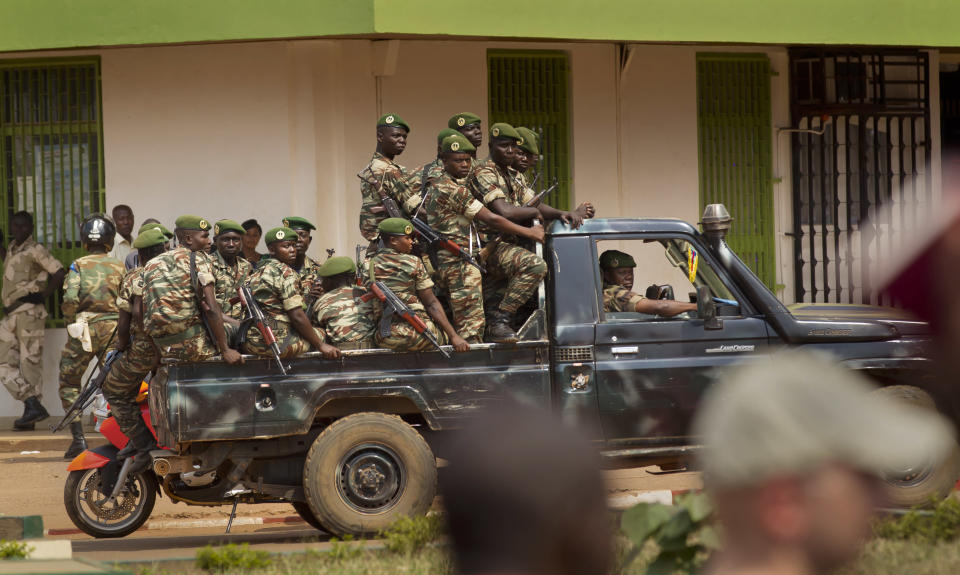 Government security forces in a pickup truck drive past a demonstration held by several hundred merchants calling for peace as negotiators prepare for talks with rebels from the north, in downtown Bangui, Central African Republic Saturday, Jan. 5, 2013. The U.N. Security Council urged rebels in the Central African Republic on Friday to halt their military offensive, withdraw from cities they have seized, and take part in negotiations to find a political solution to the impoverished country's longstanding problems. (AP Photo/Ben Curtis)