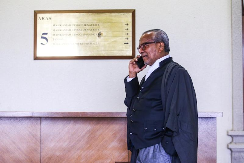 Tan Sri Muhammad Shafee Abdullah makes a call at the Kuala Lumpur Courts Complex August 19, 2019. — Picture by Hari Anggara