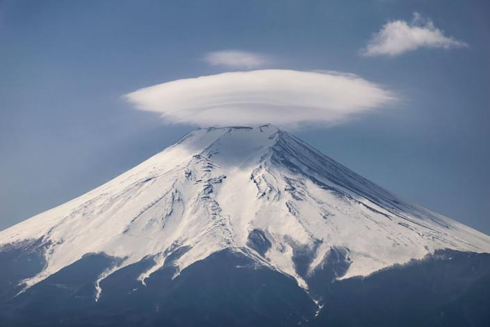 Mount Fuji creates two types of lenticular clouds. One is called Kasagumo (umbrella cloud) and appears on top of Fuji. The other is called Tsurushigumo and shows up in the lee. Fuji created a huge Tsurushigumo this morning and it became pink just before the sunrise.