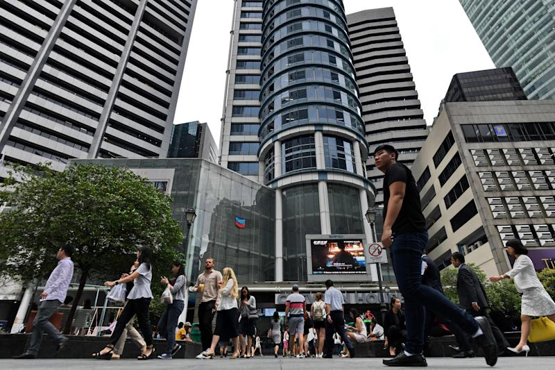 People walk along the Raffles Place business district in Singapore on September 5, 2018. (Photo by Roslan RAHMAN / AFP) (Photo credit should read ROSLAN RAHMAN/AFP/Getty Images)