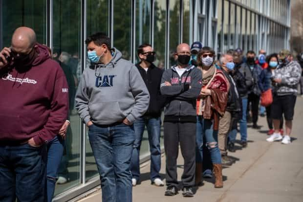 People line up outside an immunization clinic to get their Oxford-AstraZeneca COVID-19 vaccine in Edmonton on April 20, 2021.