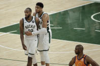 Milwaukee Bucks forward Khris Middleton celebrates with teammate forward Giannis Antetokounmpo, right, at the end of Game 4 against the Phoenix Suns in basketball's NBA Finals Wednesday, July 14, 2021, in Milwaukee. (AP Photo/Aaron Gash)