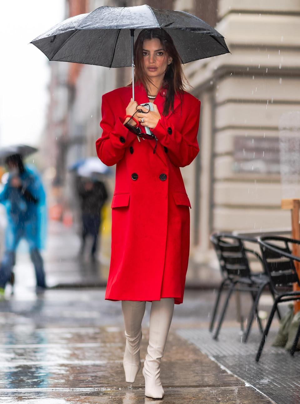<p>Emily Ratajkowski braves the rain in an elegant red coat and white boots on Thursday in N.Y.C. </p>