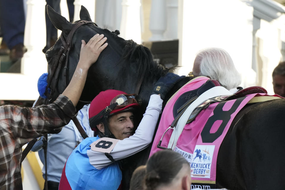 Jockey John Velazquez hugs Medina Spirit in the winner's circle after winning the 147th running of the Kentucky Derby at Churchill Downs, Saturday, May 1, 2021, in Louisville, Ky. (AP Photo/Jeff Roberson)