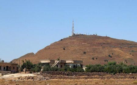 Syrian villagers walk near the border between Syria and the Israeli-occupied Golan Heights in Quneitra