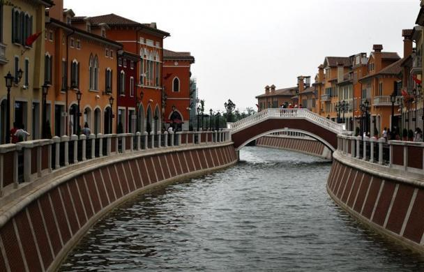 A bridge crosses a canal that flows through the center of the Florentia Village in the district of Wuqing, located on the outskirts of the city of Tianjin, China, June 13, 2012. The shopping center, which covers an area of some 200,000 square meters, was constructed on a former corn field at an estimated cost of US$220 million and copies old Italian-style architecture with Florentine arcades, a grand canal, bridges, and a building that resembles a Roman Coliseum.