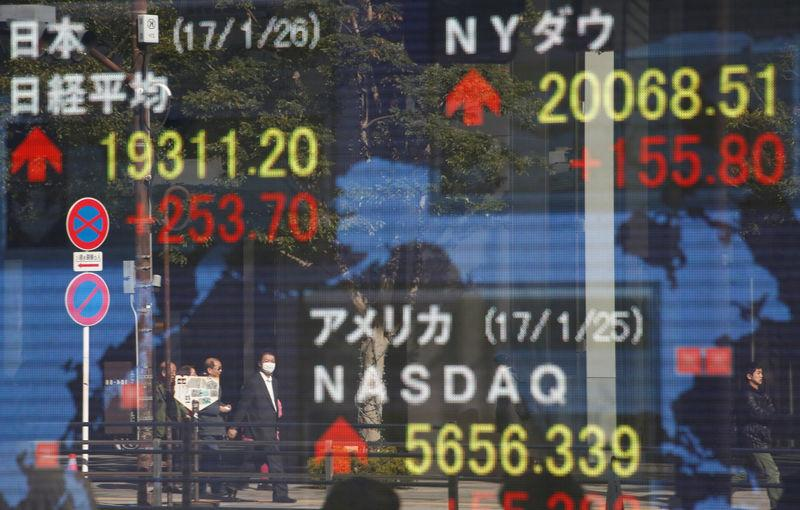 Pedestrians are reflected on an electronic board showing Japan's Nikkei average, the Dow Jones average and the stock averages of other countries outside a brokerage in Tokyo