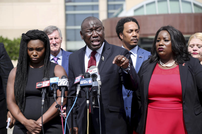 Attorney Benjamin Crump, center, flanked by Britany Jacobs, left, and Clearwater attorney Michele Rayner, right, speaks to the media at the Pinellas County Criminal Justice Center Thursday, July 26, 2018, in Clearwater, Fla. Crump, an attorney for the family of Markeis McGlockton, an unarmed black man fatally shot by a white man in a Florida parking lot said Thursday that race is the reason no charges have been filed after the videotaped altercation. (Douglas R. Clifford/Tampa Bay Times via AP)