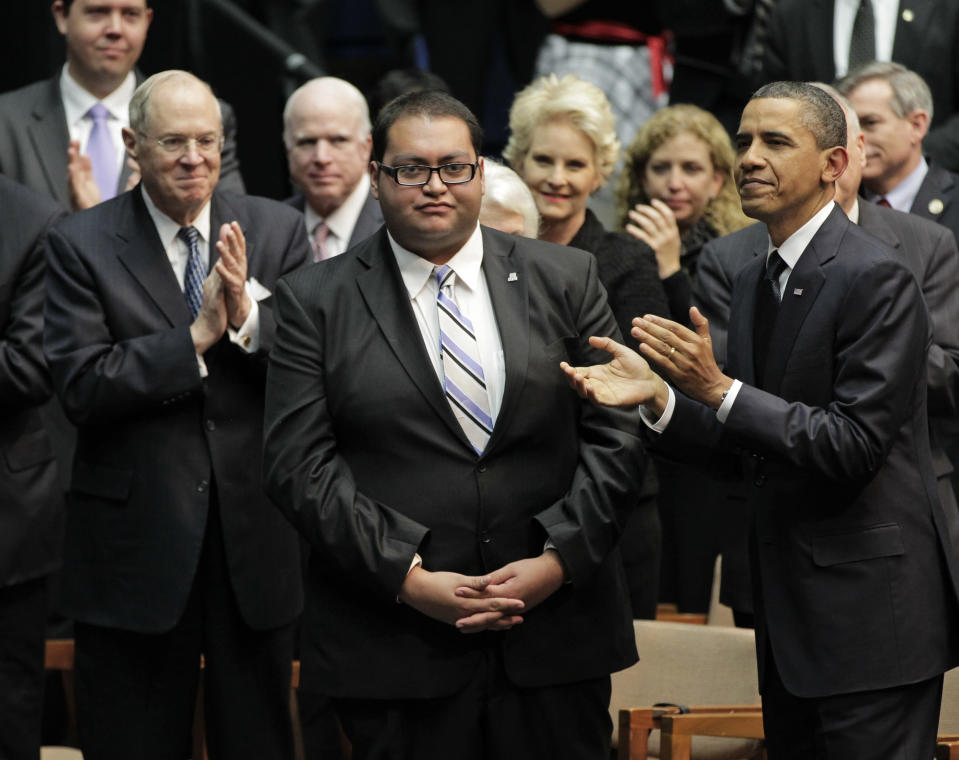 FILE - In this Jan. 12, 2011 file photo, Daniel Hernandez Jr., center, who was with Rep. Gabrielle Giffords when she was shot, receives a standing ovation, during President Obama's visit to speak in Tucson, Ariz., in the wake of the mass shooting. Hernandez Jr., announced Thursday, May 20, 2021, he's running to represent Giffords former district in Congress. (AP Photo/J. Scott Applewhite, File)