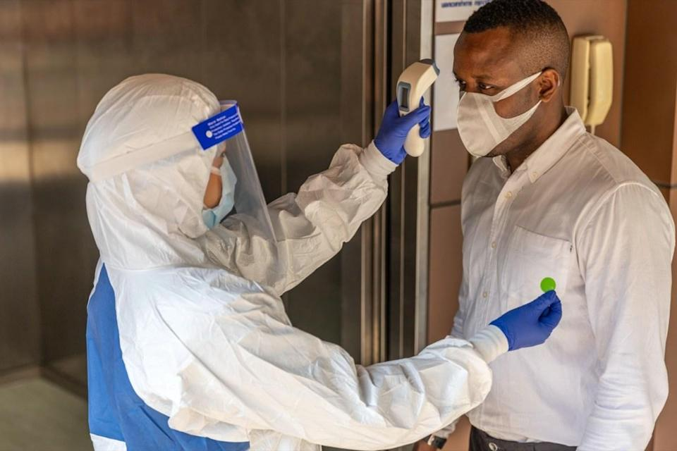 Guard in PPE suit uses infrared thermometer measuring temperature with African male worker scanning for Coronavirus or Covid-19 symptom at office elevator International medical healthcare system