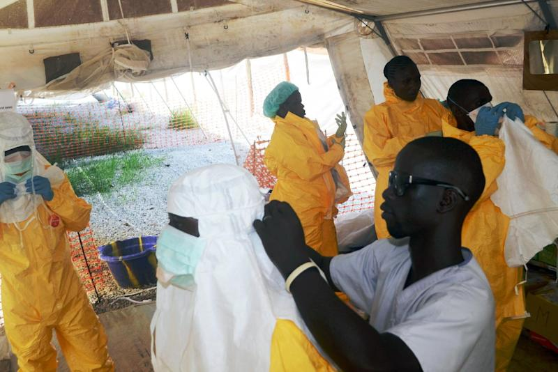 Members of Doctors Without Borders putting on protective gear at the isolation ward of the Donka Hospital in Conakry on June 28, 2014