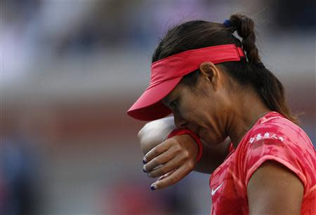 Li Na of China wipes her face during her match against Serena Williams of the U.S. at the U.S. Open tennis championships in New York
