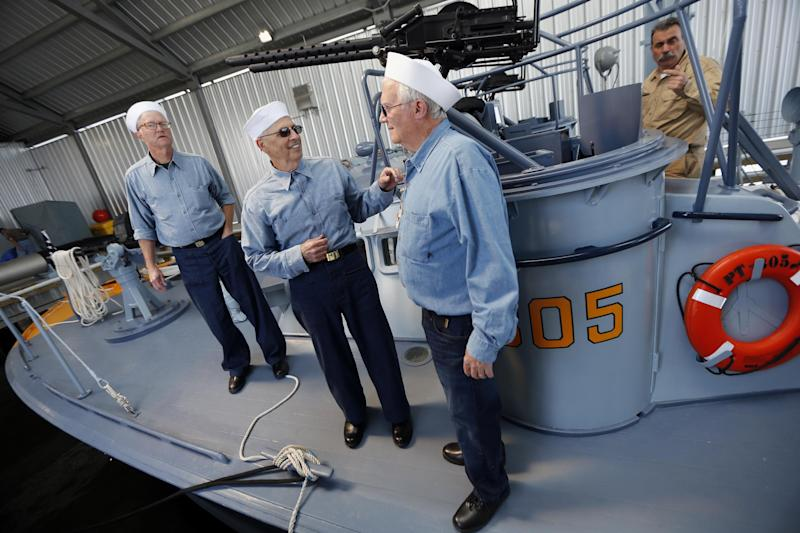 Crew members, left to right, Dave Finney, Frank Curry and Warren Blackwell, chat after a media ride of the PT 305, which was restored by the National WWII Museum, on Lake Pontchartrain, where she was originally tested by Higgins Industries more than 70 years ago, in New Orleans, Thursday, March 16, 2017. The U.S. Navy PT boat that sank three vessels and saw action in Europe in World War II is back in New Orleans where it was built, what historians describe as the nation's only fully restored combat ship of that type from the era. Its return to water is the culmination of a 10-year restoration project by the museum. (AP Photo/Gerald Herbert)