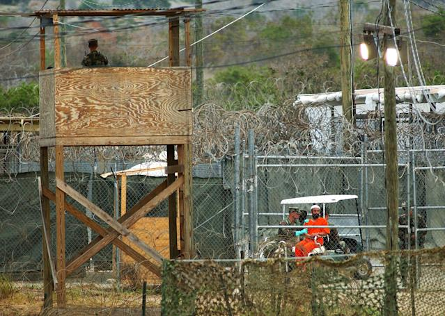 402993 01: A Camp X-Ray detainee (R) is transported in an electric cart March 27, 2002 in Guantanamo Bay, Cuba. Over 300 detainees are being held at the camp as work continues on a more permanent prison nearby. (Photo by Chris Hondros/Getty Images)
