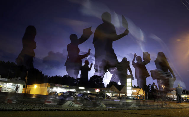 <p>Protesters march in the street as lightning flashes in the distance in Ferguson, Mo. on Aug. 20, 2014. On Aug. 9, 2014, white police officer Darren Wilson fatally shot Michael Brown, an unarmed black 18-year old. (AP Photo/Jeff Roberson) </p>