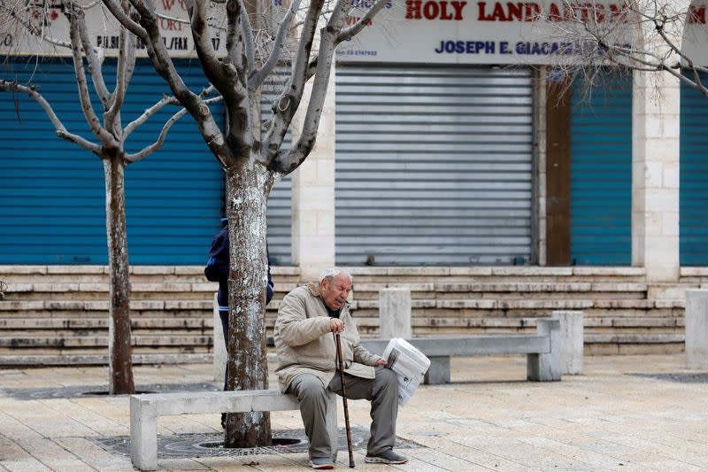 man sits in front of closed shops as preventive measures are taken against the coronavirus, in Bethlehem in the Israeli-occupied West Bank