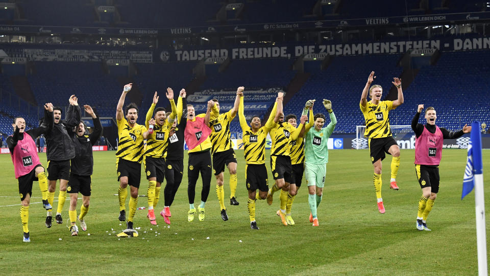 Dortmund players celebrate at the end of the German Bundesliga soccer match between FC Schalke 04 and Borussia Dortmund in Gelsenkirchen, Germany, Saturday, Feb. 20, 2021. Dortmund won 4-0. (AP Photo/Martin Meissner, Pool)
